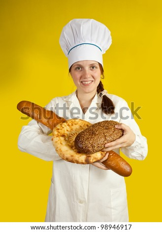 female baker with hands full of bread over yellow