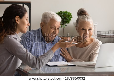 Female banking specialist consult happy mature couple about loan or mortgage at meeting in office. Woman consultant advise recommend elderly spouses good medical life health insurance on computer.