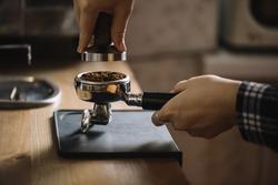 Female barista tamping coffee in a portafilter