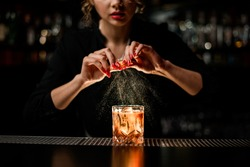 female bartender gently sprinkles orange peel juice on glass with cold alcoholic cocktail on the bar counter