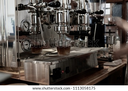 Female bartender in the workplace. Girl makes coffee using coffee machine.  #1113058175