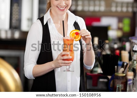 Female bartender making a tropical fruit cocktail holding an elegant long glass of beverage in her hand as she adds the sliced orange garnish to the rim