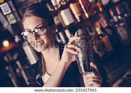 Female Bartender Making Cocktail Using Shaker In Pub.