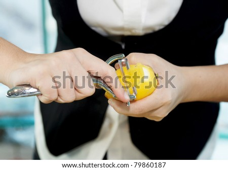 Female bartender peeling lemon to make cocktail