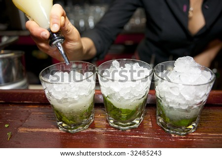 Female bartender pouring juice in glass, retro styled bar