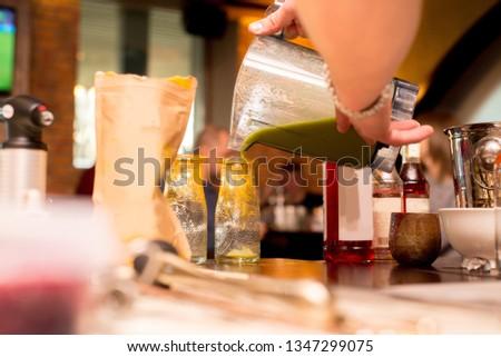 female bartender preparing cocktail in a cocktail bar #1347299075