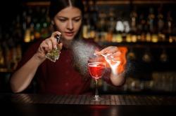 Female bartender sprinkling a cocktail glass with tasty Aperol syringe cocktail with a peated whisky and making a smoky note on the bar counter