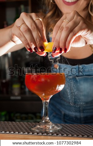 Female bartender zests a lemon rind onto  a red cocktail in a champagne glass at a bar. #1077302984