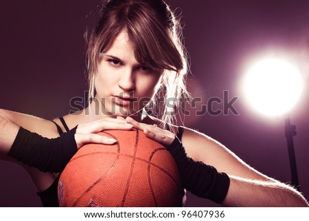 female basketball player holding ball, in black background