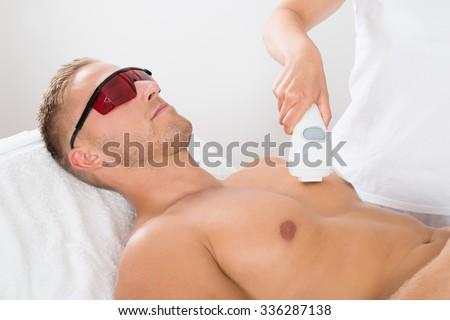 Female Beautician Giving Laser Epilation On Man\'s Chest