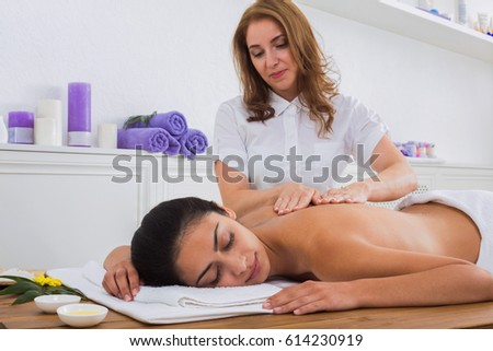 Female beautician make body back and shoulders massage to beautiful indian girl in health club or beauty parlor. #614230919