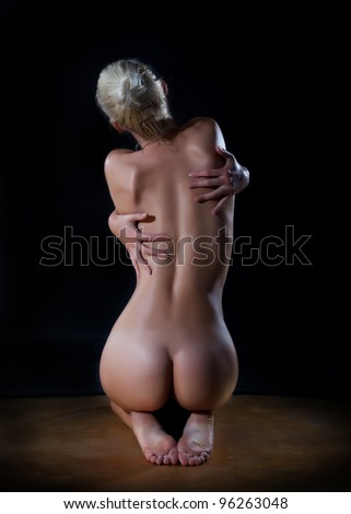 Female beautiful nude woman hugging her back over black background