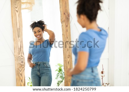 Female Beauty And Self-Confidence. Cheerful African Lady Posing Near Mirror After Slimming And Successful Weight Loss Standing At Home. Perfect Size Concept. Selective Focus Stock foto ©