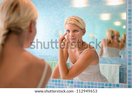Female beauty, beautiful young caucasian woman applying cream on face in bathroom at home - stock photo