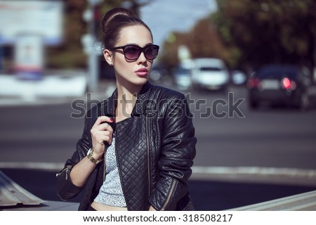 Female beauty concept. Portrait of fashionable young girl in casual black jeans, black jacket, white crop-top, sunglasses and small  bag posing on the street. Perfect hair. Vogue style. outdoor shot