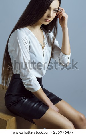Female beauty concept. Portrait of fashionable young girl in classic clothes posing over grey background. Perfect hair & skin. Vogue style. Studio shot