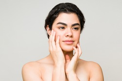 Female beauty model feeling her glowing and luminous skin after a beauty treatment at the spa. Hispanic young woman with bare shoulders