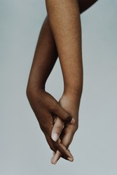 Female black and brown hands entwined. Women of color holding hands showing friendship and support. People of color, hand in hand, diversity, freedom, anti racism concept