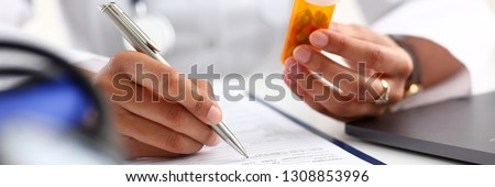 Female black medicine doctor hand hold jar of pills and write prescription to patient at worktable. Panacea and life save, prescribing treatment legal drug store concept. Empty form ready to be used