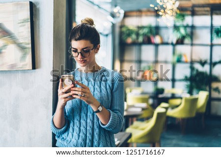 Female blogger chatting with followers in social networks on modern smartphone using 4G internet connection.Hipster girl in stylish eyeglasses watching video on website on cellular standing in cafe