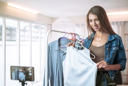 Female bloggers review clothes to customer by talking mobile live recording video on social network, modern businesswoman, social media for marketing.