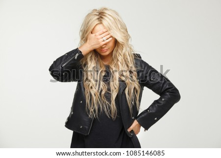 female blond is desperately puts hand on face, being disappointed in a result bad news. Sadness, loss of strength and lack of motivation.