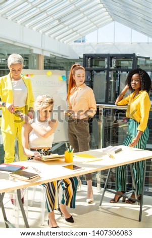 female blond secretary giving phone to her leader while sitting at the table.flipchart in the background of the photo stock photo