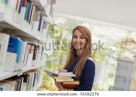female blonde college student taking book from shelf in library and looking at camera. Horizontal shape, side view, waist up