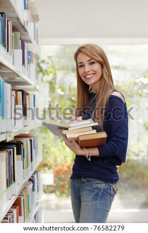 female blonde college student taking book from shelf in library and looking at camera. Vertical shape, side view, waist up