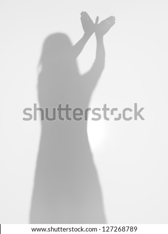female body silhouette creating a shape of a flying bird with her hands, behind a diffuse surface