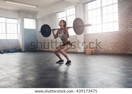 Female bodybuilder doing exercise with a heavy weight bar in gym. Full length shot of fitness woman practicing weightlifting at health club.