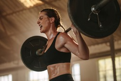 Female bodybuilder doing exercise with heavy weight bar. Fitness woman sweating from squats workout at gym. Female putting effort and screaming while exercising with heavy weights.