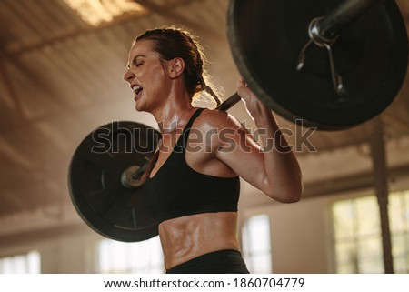 Female bodybuilder doing exercise with heavy weight bar. Fitness woman sweating from squats workout at gym. Female putting effort and screaming while exercising with heavy weights. Photo stock ©
