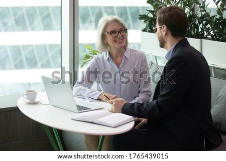 Female boss discusses work issues with subordinate middle aged man, sitting at the table. Communication and negotiations between management and employee Foto d'archivio ©