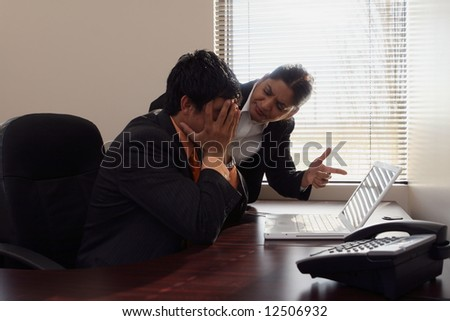 Female boss dressing down a younger male subordinate while pointing a finger at his laptop screen
