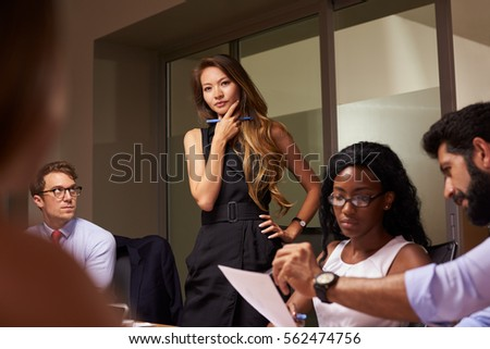 Female boss stands thinking at an evening business meeting #562474756