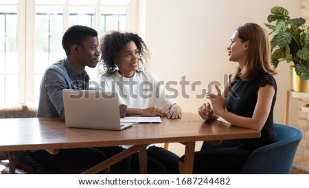 Female broker makes offer to young African ethnicity married couple during meeting in company office. Family taking loan in bank, listening advisor, real estate agent and customers negotiating concept