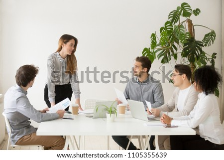 Female business coach making presentation to office workers at meeting, giving handouts to employees, team leader presenting company financial statistics to colleagues. Concept of leadership #1105355639
