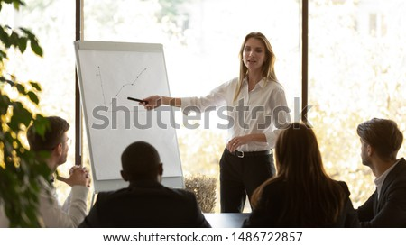Female business coach speaker pointing on flip chart presenting work results graph at conference office meeting, businesswoman mentor presenter training staff group at corporate workshop presentation