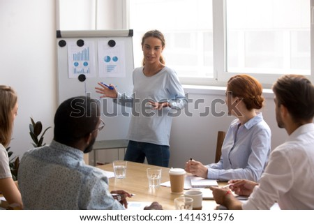 Female business coach standing near whiteboard with diagram and chart talking to diverse team in conference room. Project results presentation, explanation marketing idea, staff training concept