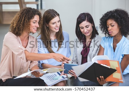 Female business colleagues interacting with each other in office stock photo