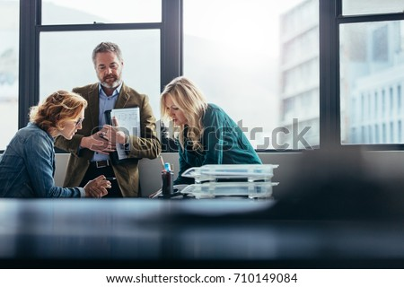 Female business colleagues working together in office. Business people discussing about project.