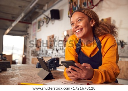 Female Business Owner In Workshop Using Digital Tablet And Holding Mobile Phone Stockfoto ©