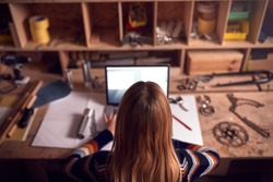 Female Business Owner Working Late In Carpentry Workshop Using Laptop