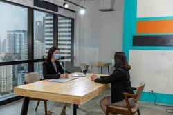 Female business workers wearing face mask and clear shield having discussion through glass partition at the office as part of business in new normal during the outbreak of COVID-19 or Coronavirus