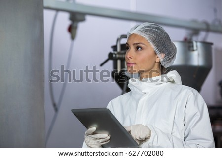 Female butcher using digital tablet at meat factory