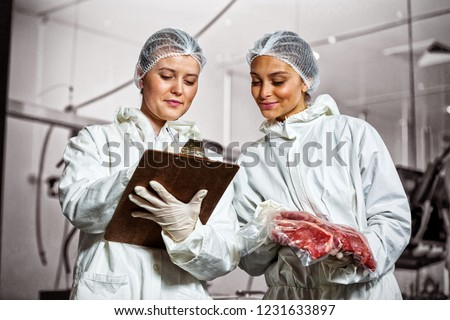 Female butchers maintaining records on clipboard at meat factory