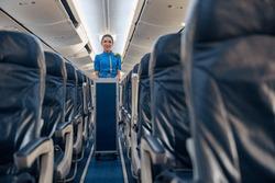 Female cabin attendant leading trolley cart through empty plane aisle. Travel, service, transportation, airplane concept