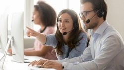 Female call center agent operator telemarketer helping male colleague teaching new worker online customer support pointing at computer, business team in wireless headset talk working together on pc