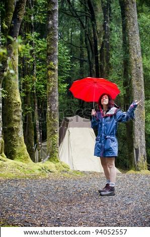 Female camper holding red umbrella checking for rain near rain forest trees near Queenstown, Tasmania, Australia